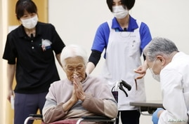 An elderly woman gestures to express gratitude after receiving a coronavirus disease (COVID-19) vaccination in Itami, western…