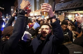 People hold up beverages as they party on a street in Soho, as the coronavirus disease (COVID-19) restrictions ease, in London.