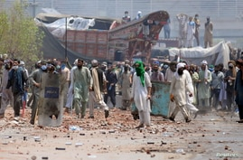 Supporters of the banned Islamist political party Tehrik-e-Labaik Pakistan (TLP) with sticks and stones block a road during a…