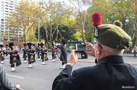 A veteran films a band with his phone as Australian military personnel, past and present, commemorate ANZAC Day during a march…