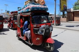 Residents ride in rickshaws as they flee following renewed clashes between rival factions in the security forces, who have…