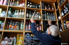 """Mustafa Demirci arranges bottles of alcoholic beverages at his liquor shop ahead of a nationwide """"full closure"""" amid the spread…"""