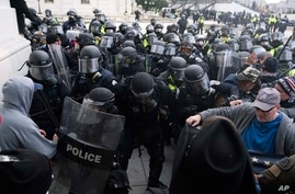 FILE - In this Jan. 6, 2021, file photo, U.S. Capitol Police push back rioters trying to enter the U.S. Capitol in Washington…