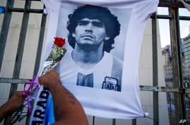 A man places a flower on a jersey with the face of late soccer star Diego Maradona during a march to demand answers regarding…