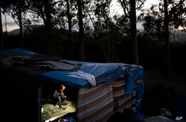 A migrant rests in a makeshift shelter in Las Raices camp in San Cristobal de la Laguna on the Canary Island of Tenerife, Spain, March 17, 2021.
