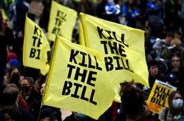 Demonstrators hold flags during a 'Kill the Bill' protest in London, Saturday, April 3, 2021. The demonstration is against the…