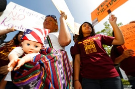 FILE - In this July 3, 2014, file photo, immigration activists Amarily Ortiz, left, and Mayra Sixtos, demand the Mexican…