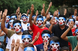 Young demonstrators flash the three-fingered symbol of resistance during an anti-coup mask strike in Yangon, Myanmar, Sunday,…