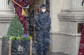 Snow falls as a police officer stands in front of the Grand Hotel Wien where closed-door nuclear talks with Iran take place in…