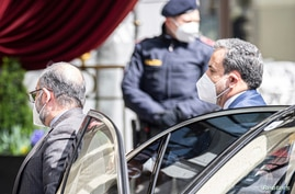 Political deputy at the Ministry of Foreign Affairs of Iran, Abbas Araghchi, right, arrives at the Grand Hotel Wien.