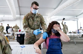 FILE - In this April 5, 2021, file photo, Leanne Montenegro, 21, covers her eyes as she doesn't like the sight of needles,…