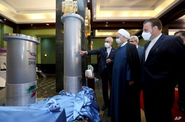 FILE - Iranian President Hassan Rouhani, second from right, listens to the head of the Atomic Energy Organization of Iran Ali Akbar Salehi while visiting an exhibition of Iran's new nuclear achievements in Tehran, Iran.