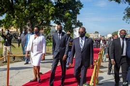 FILE - Haiti's President Jovenel Moise, center, accompanied by his wife Martine, and Prime Minister Joseph Jouthe, center right.