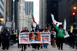 Protesters holding signs navigate along Chicago's South Michigan Avenue during a peaceful protest, Wednesday, April 14, 2021,…