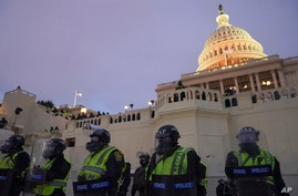 In this Wednesday, Jan. 6, 2021, photo, police form a line to guard the Capitol after violent rioters stormed the Capitol, in…