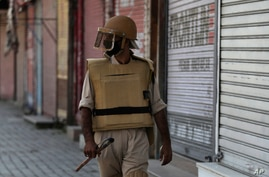 FILE- In this Thursday, Aug. 22, 2019 file photo, a Kashmiri policeman patrols outside closed shops in Srinagar, Indian…