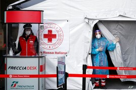 Paramedics wait to perform a COVID-19 swab test on passengers inside a tent settled outside the Milan's central railway station…
