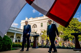 President Joe Biden and Japanese Prime Minister Yoshihide Suga leave a news conference in the Rose Garden of the White House in…