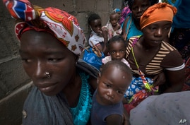 Displaced women with their children wait for assistance at a building used by refugees as shelter in Pemba, Mozambique, after…