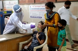 A girl reacts as a health worker collects her swab sample to test for COVID-19 in Mumbai, India, Tuesday, April 20, 2021. …