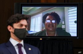 Stacey Abrams testifies remotely via video conference as Sen. Jon Ossoff, D-Ga., listens during a Senate Judiciary Committee.