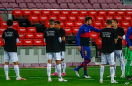 """Getafe players wearing t-shirts that read in Spanish: """"Football for the fans"""" welcome into the pitch FC Barcelona players prior…"""