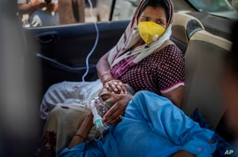 A patient breathes with the help of oxygen provided by a Gurdwara, Sikh place of worship, inside a car in New Delhi, India,…