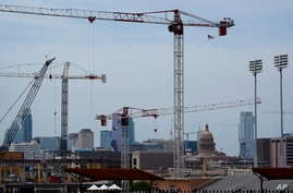 Construction cranes hover over downtown and near the State Capitol, Monday, April 26, 2021, in Austin, Texas. Texas' torrid…