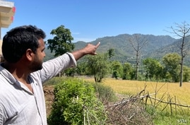 A young Kashmiri pointing toward the Indian army posts on the hilltops lining the de facto Kashmir frontier with Pakistani-administered part of the divided region. (Ayaz Gul/VOA)