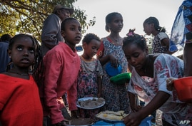 Displaced children from Western Tigray gather at meal time to receive food outside a classroom in the school where they are sheltering in Tigray's capital Mekele, Ethiopia, Feb. 24, 2021.