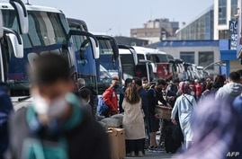 Travelers wait to board buses as they prepare to leave Istanbul from the city's Esenler national bus station, April 29, 2021, ahead of a new national COVID lockdown.