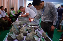 FILE - Buyers checks jade stones before the auction during the annual Myanmar Jade, Gems and Pearl Emporium in Naypyidaw, Sept. 16, 2019.