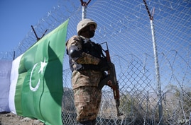 FILE - A Pakistani soldier stands guard next to a fence along Pakistan's border with Afghanistan's Paktika province, in Angoor Adda, in Pakistan's South Waziristan tribal agency, Oct. 18, 2017.