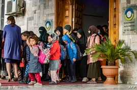 Children walk out of a building during the handover of orphaned children, whose parents were suspected of belonging to the Islamic State group, to a Russian delegation by Syrian Kurdish officials, in Syria's northeastern city of Qamishli, April 18, 2021.