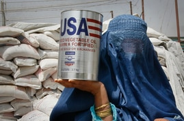 FILE - An Afghan woman carries a container of vegetable oil donated by United States Agency for International Development (USAID), in Kabul, Afghanistan, July 26, 2011.