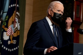 FILE - President Joe Biden removes his mask to speak at a news conference at the White House, in Washington, April 14, 2021.