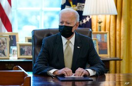 FILE - President Joe Biden is seen sitting at his desk in the Oval Office of the White House in Washington, March 30, 2021.