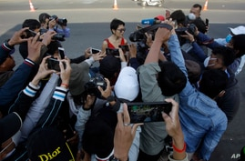 Theary Seng, rear center, a Cambodian-American lawyer, is surrounding by journalists as she talks to them in front of Phnom Penh Municipal Court, in Phnom Penh, Cambodia, Jan. 14, 2021.