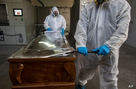 Workers open the coffin of a COVID-19 victim to place his remains into an incinerator, at La Recoleta crematorium in Santiago, Chile, April 16, 2021.