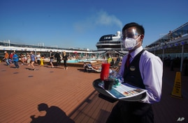 A waiter, wearing a mask for COVID-19 protection, holds a tray of drinks on the MSC Grandiosa cruise ship in Civitavecchia, near Rome, March 31, 2021.