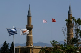 (From left to right) Greek and Cyprus' flags, a Turkish and Turkish Cypriot breakaway flags fly on a minaret of the Selimiye mosque, or Cathedral of St Sophia in divided capital Nicosia, Cyprus, April 26, 2021.