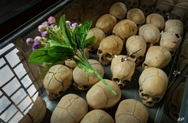 FILE - Flowers are laid on top of a glass case containing the skulls of some of those who were slaughtered as they sought refuge in a church, kept as a memorial to the thousands who were killed during the 1994 genocide, in Ntarama, Rwanda, April 5, 2019.