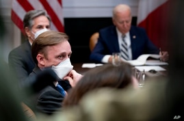 White House national security adviser Jake Sullivan, front, Secretary of State Antony Blinken, background-left, attend a meeting with President Joe Biden, right, in the Roosevelt Room of the White House, in Washington, March 1, 2021.