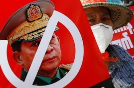 FILE - A protester holds a placard with a crossed out face of Commander in Chief, Senior Gen. Min Aung Hlaing, during an anti-coup rally in front of the Myanmar Economic Bank in Mandalay, Myanmar, Feb. 15, 2021.