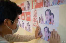 An anti-coup protester looks at the images of ousted Myanmar leader Aung San Suu Kyi during a protest against the military coup in Yangon, April 26, 2021.