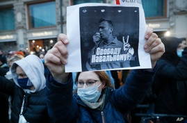 """A activist holds a poster reading """"Freedom for Navalny!"""" during the opposition rally in support of jailed opposition leader Alexei Navalny in Moscow, Russia, April 21, 2021."""