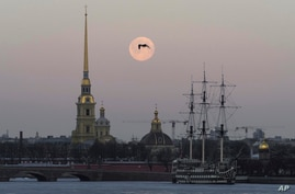 FILE - A bird is silhouetted against full moon in St. Petersburg, Russia, March 29, 2021. Russia on Saturday ordered the expulsion of Ukraine's consul in St. Peterburg for allegedly trying to obtain classified information.