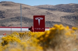 FILE - A sign marks the entrance to the Tesla Gigafactory in Sparks, Nevada, Oct. 13, 2018.