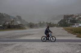 A man rides his bicycle past fields covered with volcanic ash a day after the La Soufriere volcano erupted, in Kingstown, on the eastern Caribbean island of St. Vincent, April 10, 2021.