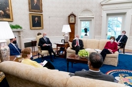 President Joe Biden meets with Transportation Secretary Pete Buttigieg, left, and members of congress to discuss his jobs plan in the Oval Office of the White House in Washington, April 19, 2021.